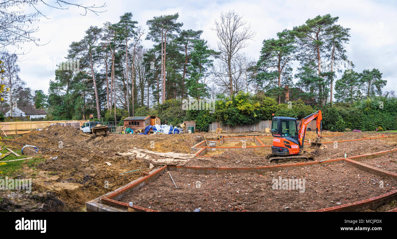Orange Hitachi heavy plant mechanical digger in the foundations of a new house under construction on a building site in Surrey, southeast England, UK - Stock Image
