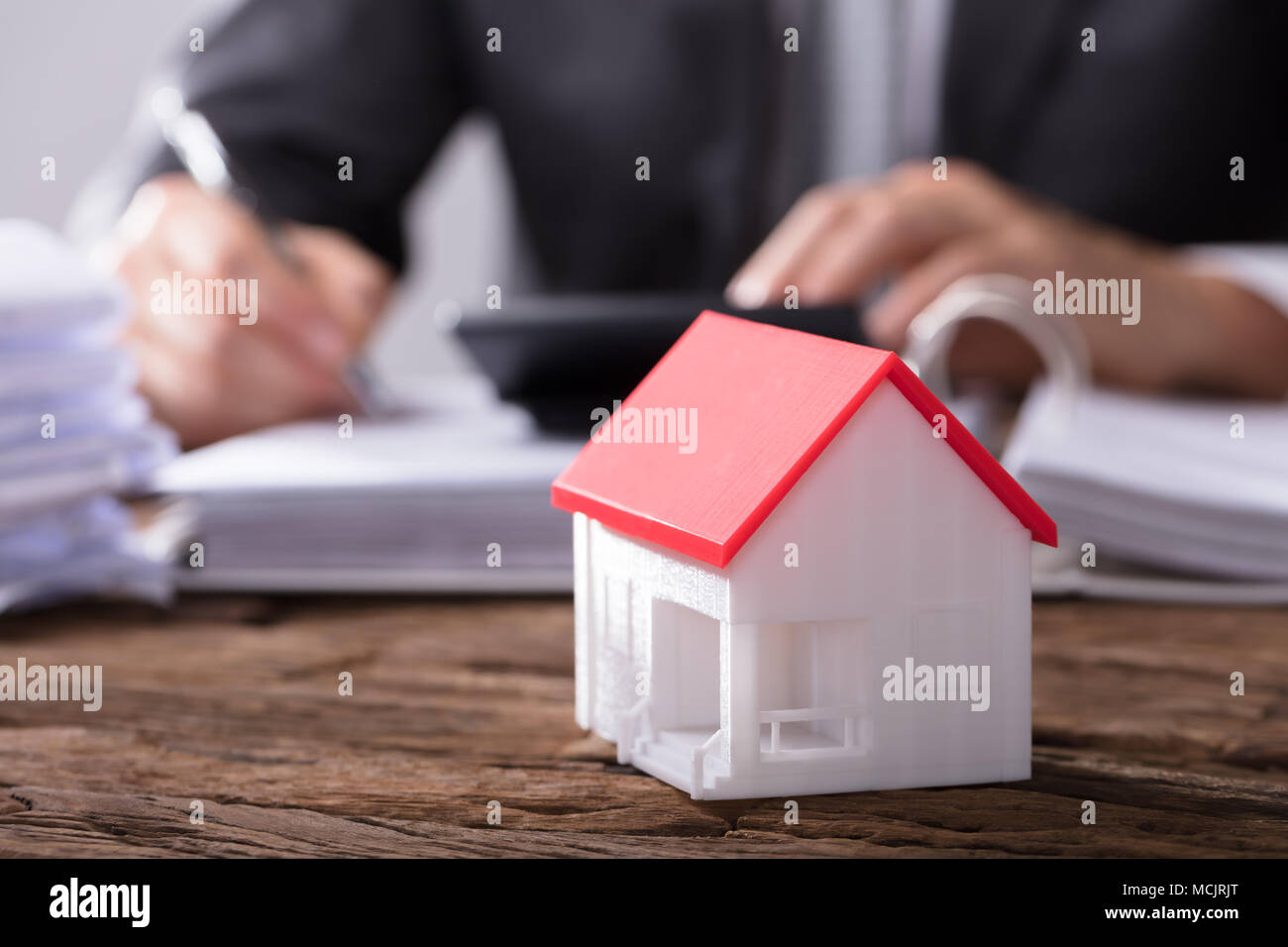Close-up Of A House Model With Red Roof On Wooden Desk - Stock Image
