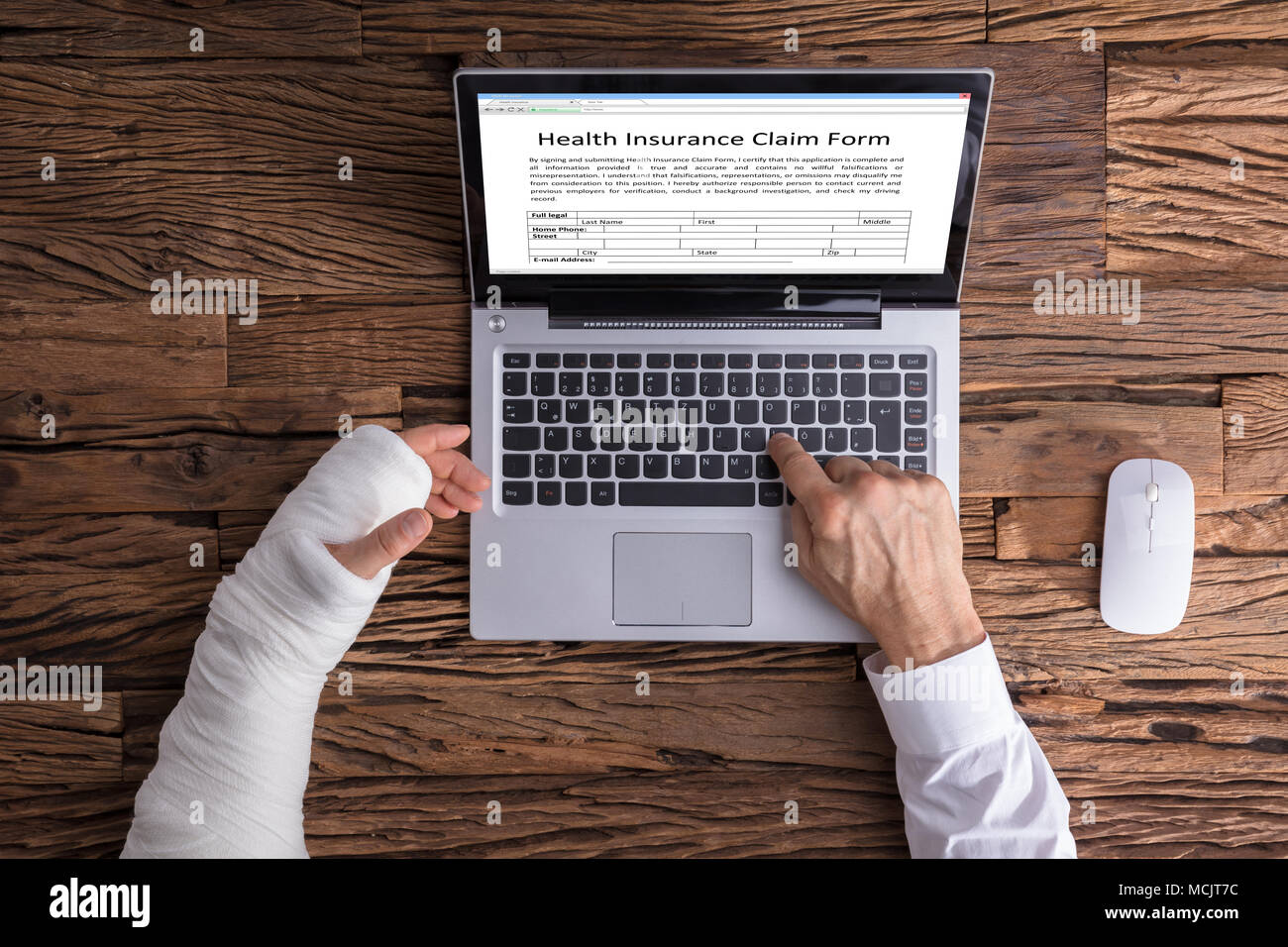 High Angle View Of A Businessperson With Hand Injury Filling Health Insurance Claim Form - Stock Image
