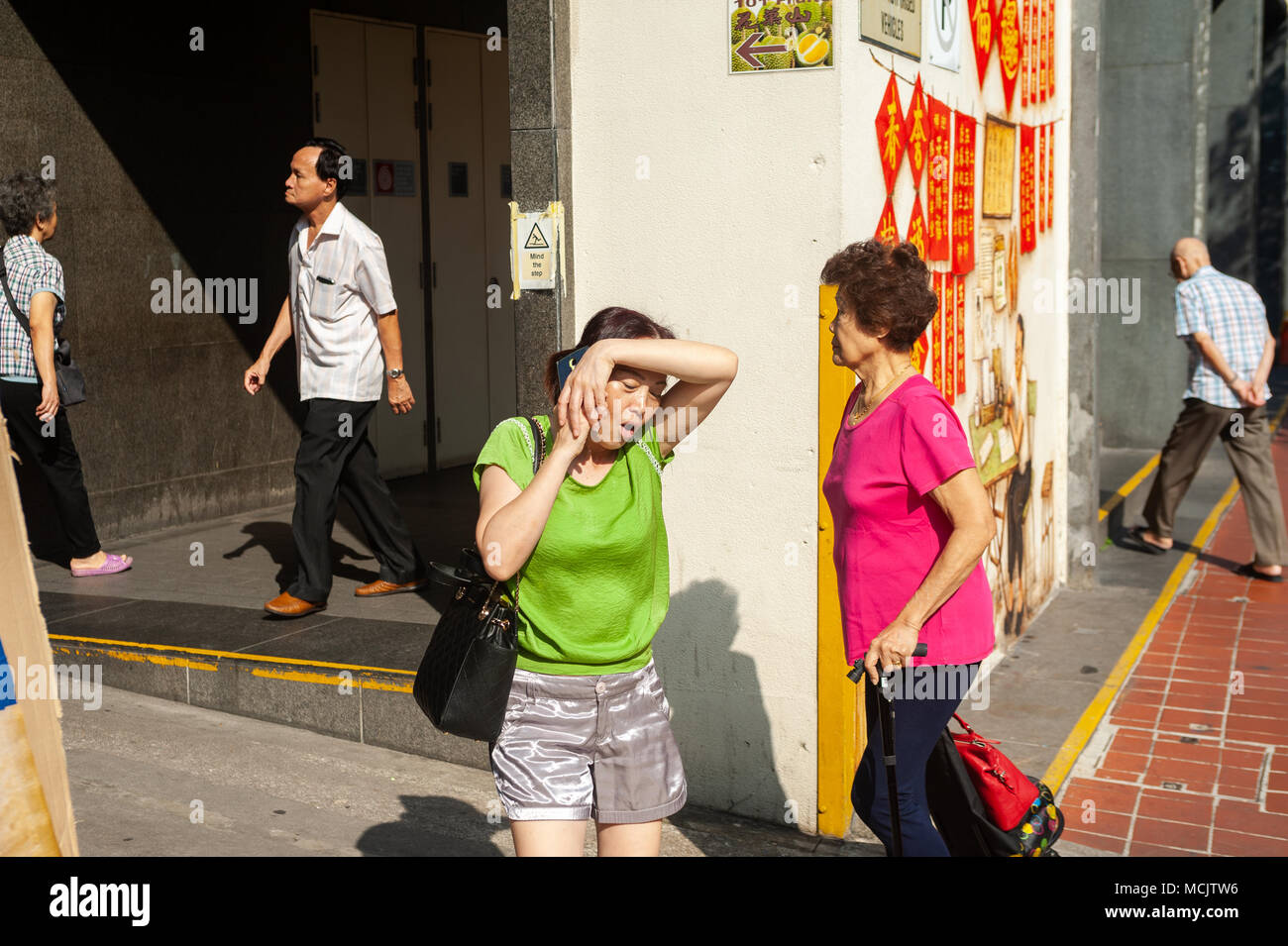 04.04.2018, Singapore, Republic of Singapore, Asia - A woman walks down a street in Singapore's Chinatown district and talks on the phone. - Stock Image