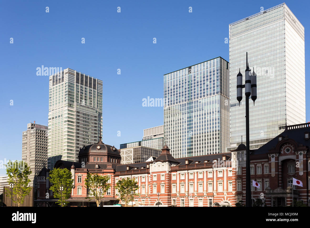 The classic architecture of the Tokyo JR train station contrasts with modern office building in the buisiness district of Marunouchi in Tokyo, Japan c - Stock Image