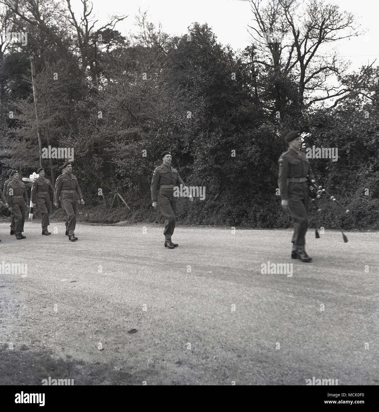1955, Bucks, England, a piper leads a troop of British soldiers along a track in a forest on a training march, - Stock Image