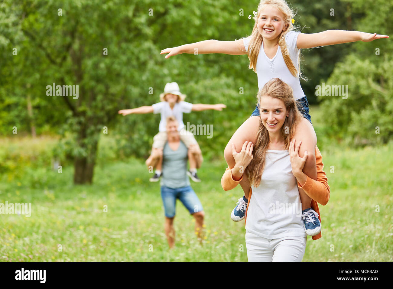 Happy kids ride piggyback on a trip with their parents - Stock Image