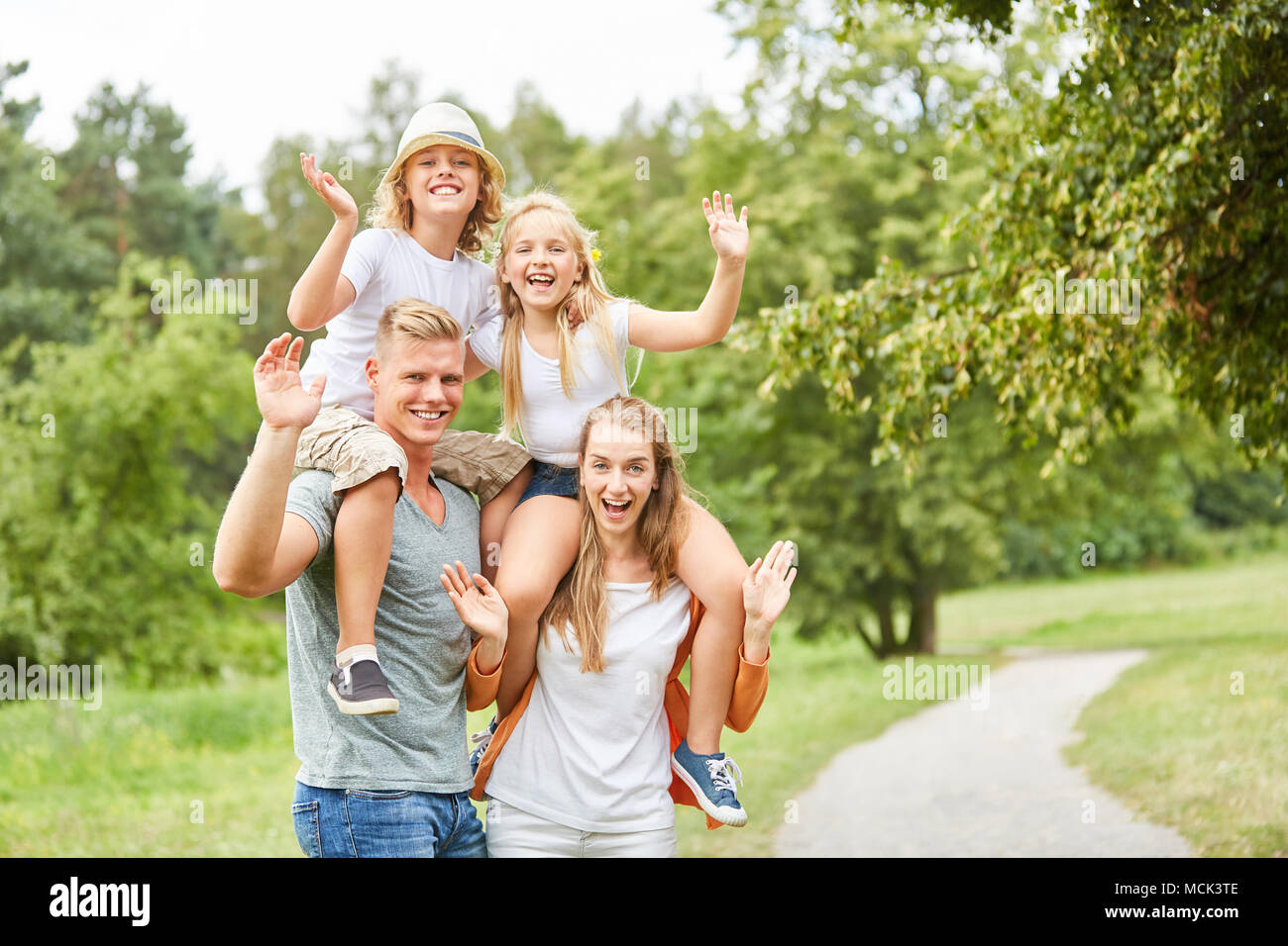 Family and children in piggyback cheerfully waving on a trip - Stock Image