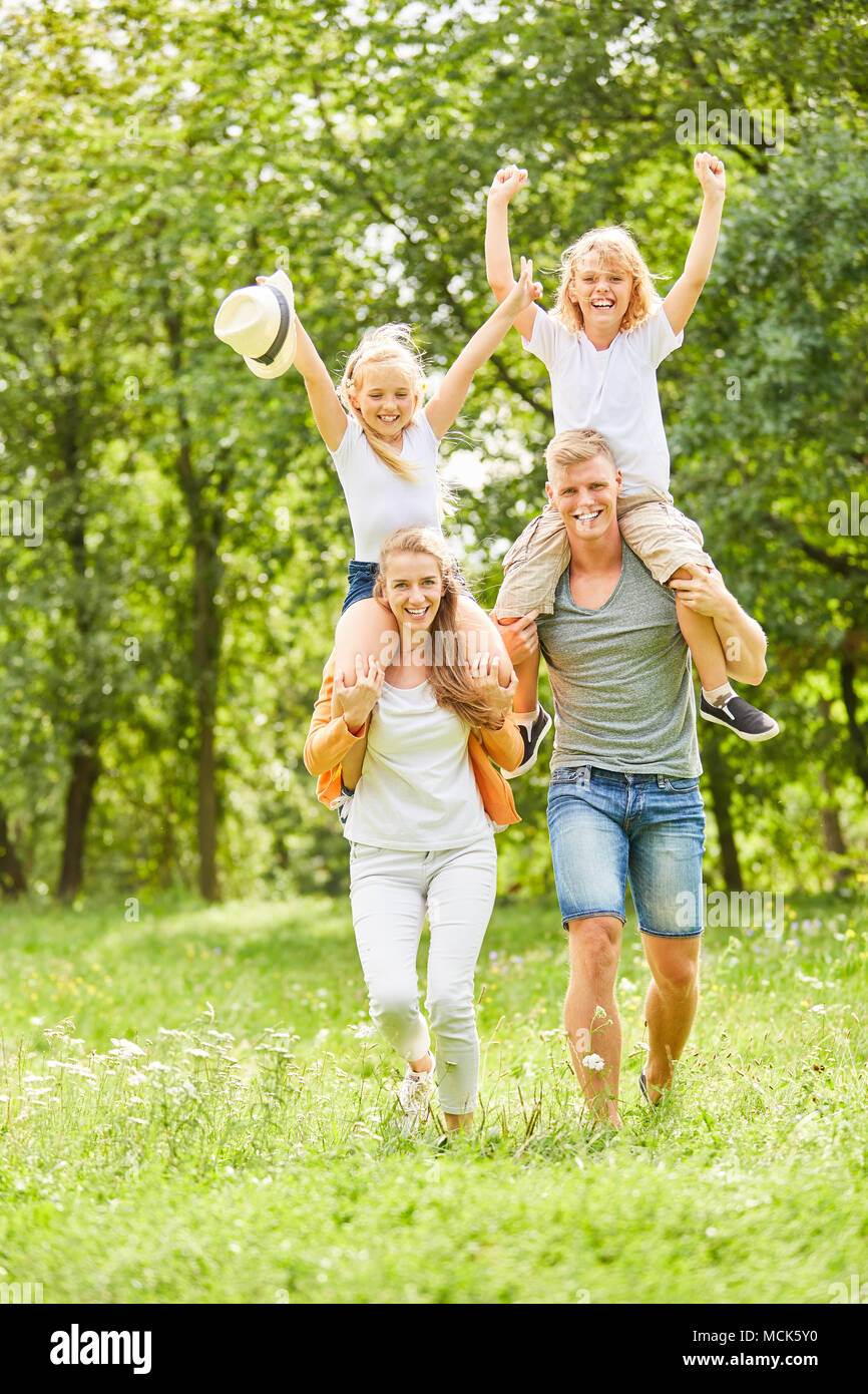 Children ride piggyback on their parents' backs and cheer - Stock Image