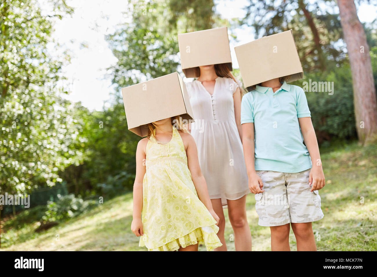Family with their faces under cardboard boxes hidden in the garden - Stock Image