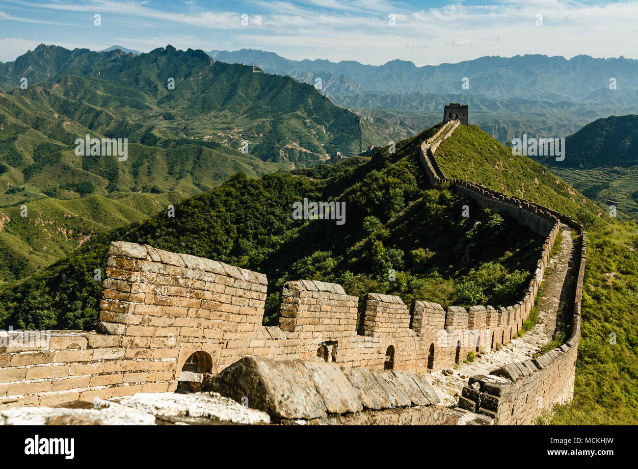 Expansive view of stretch of the Great Wall of China and green mountainous countryside - Stock Image