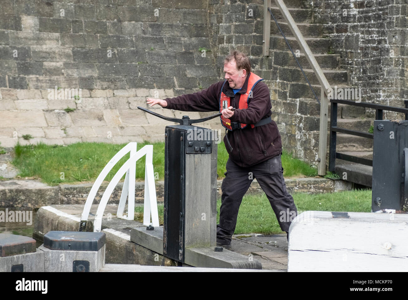 A Lock Keeper on The Five Rise Locks on the Leeds and Liverpool Canal,  Bingley, near Bradford, West Yorkshire, England. - Stock Image