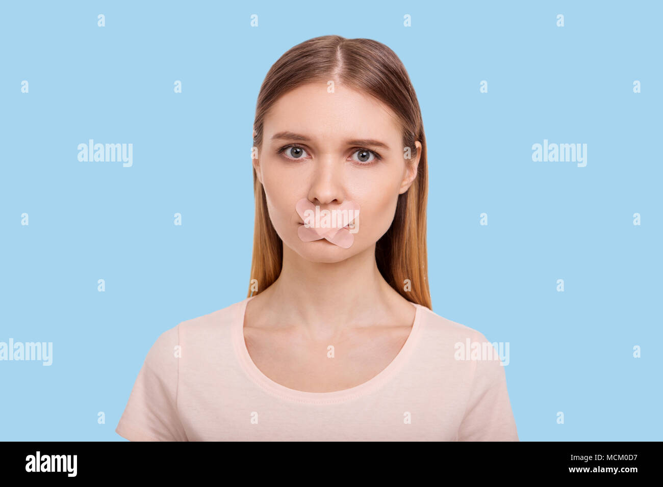 Young woman having mouth sealed with adhesive bandages Stock Photo