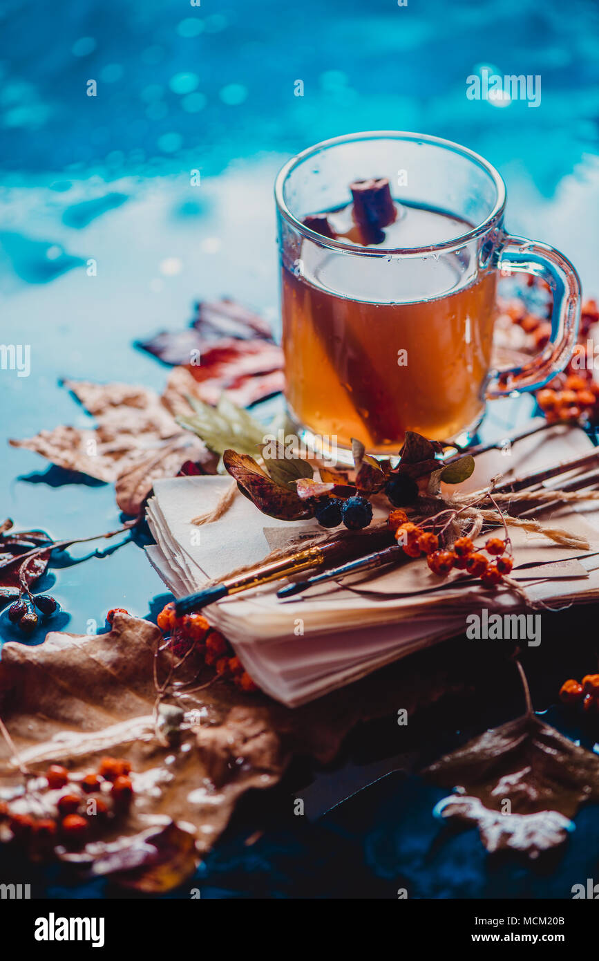 Rainy still life with a glass tea cup on a wet wooden background with copy space. Autumn concept with fallen leaves and a stack of artist scetches - Stock Image
