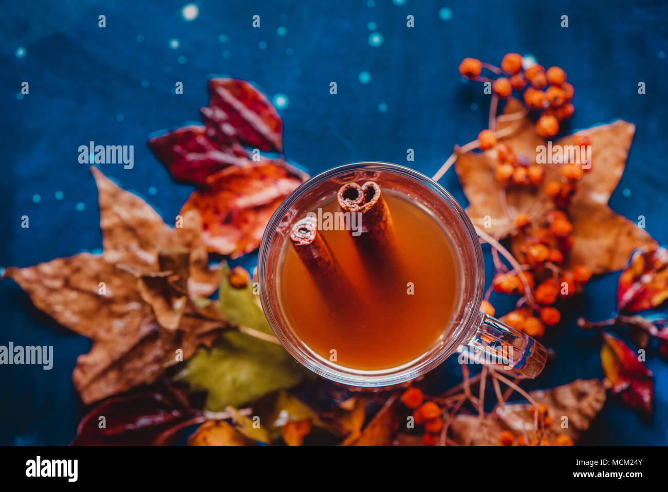 Cinnamon tea flat lay with fallen leaves. Glass tea cup on a wet wooden background with copy space. Autumn still life with herbal beverage. - Stock Image