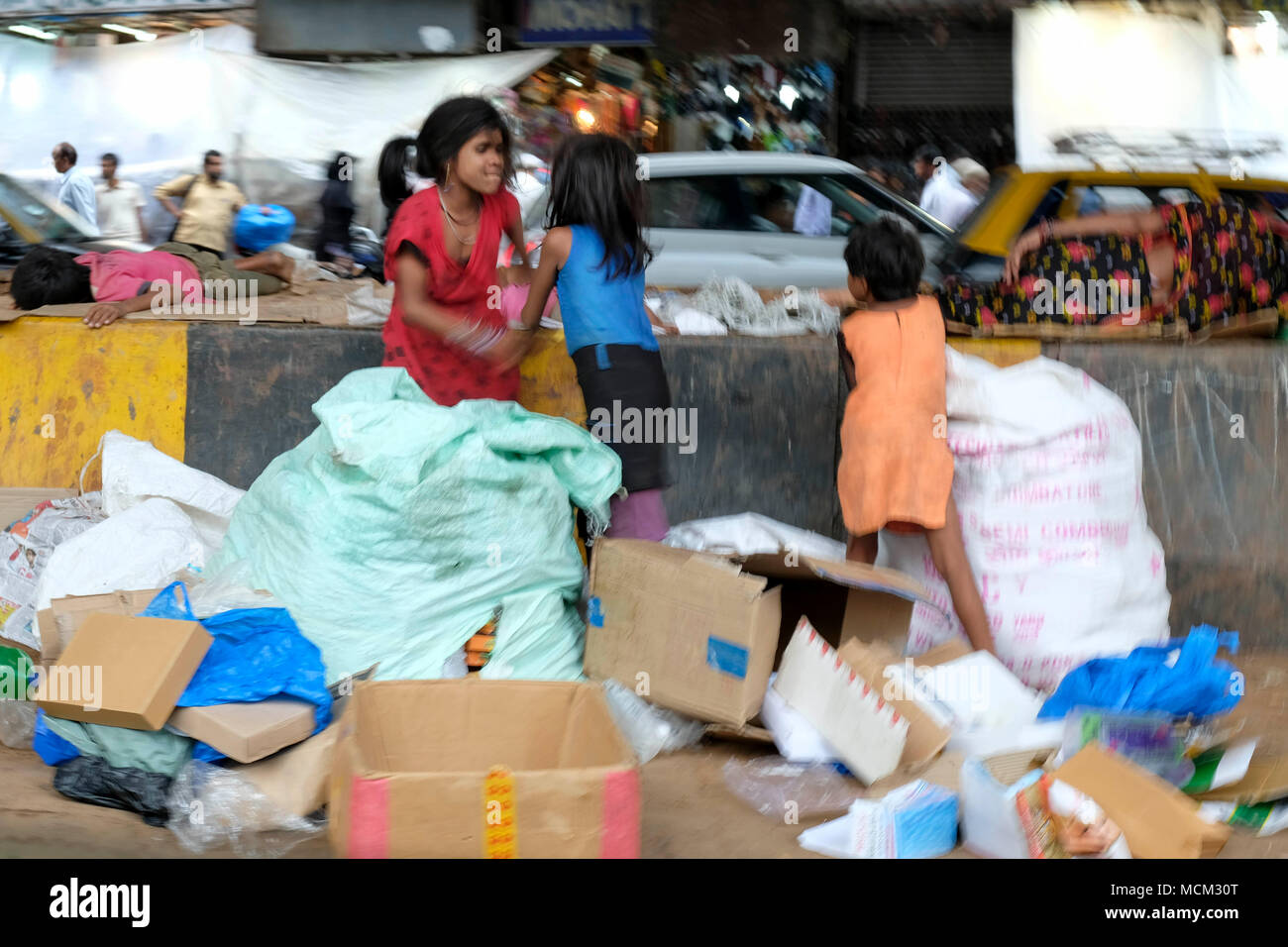 Street children working collecting cardboard and garbage in downtown Mumbai, India - Stock Image