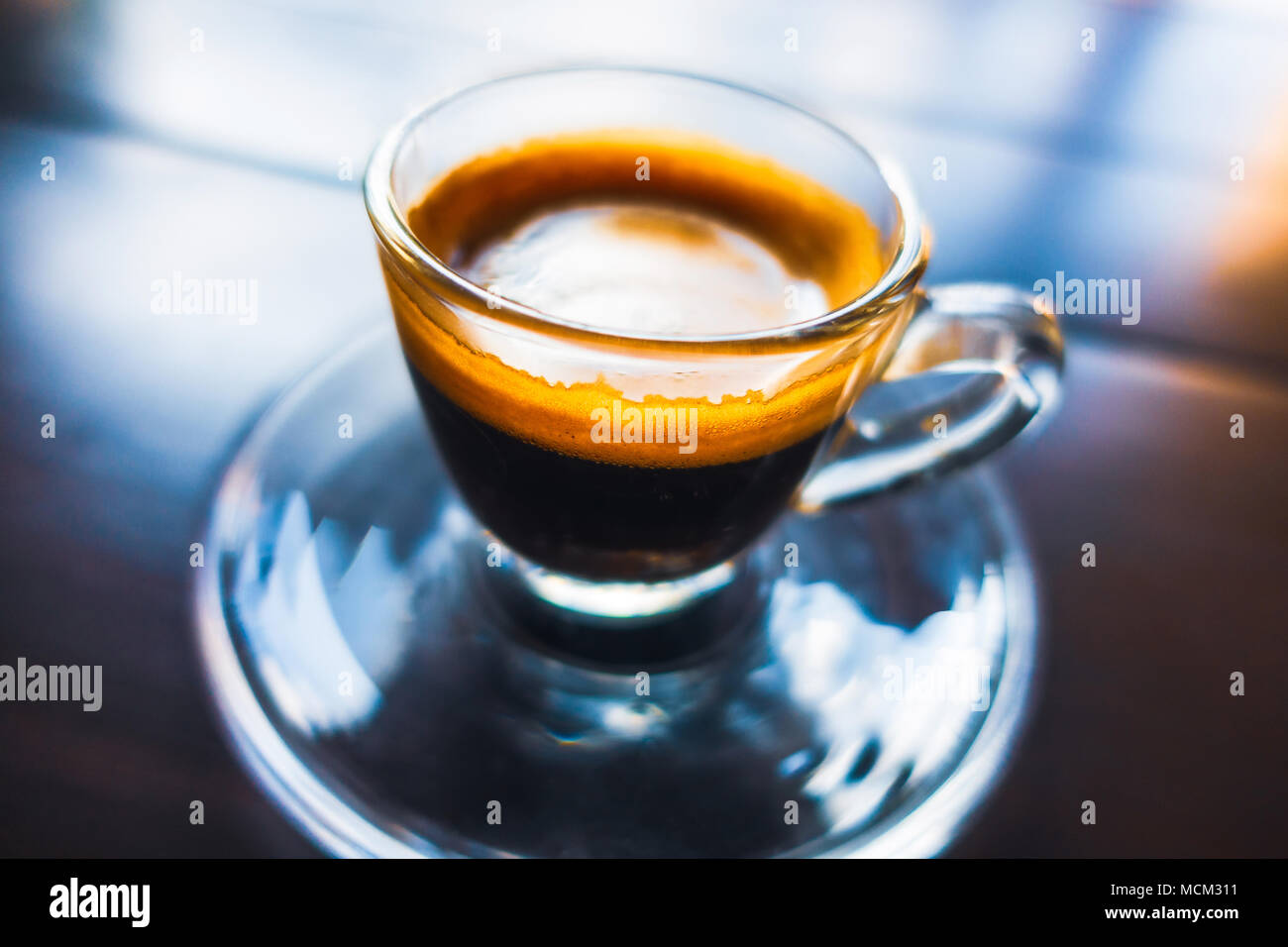 Espresso coffee in glass cup on wooden table, colorful reflections and shallow depth of field. - Stock Image