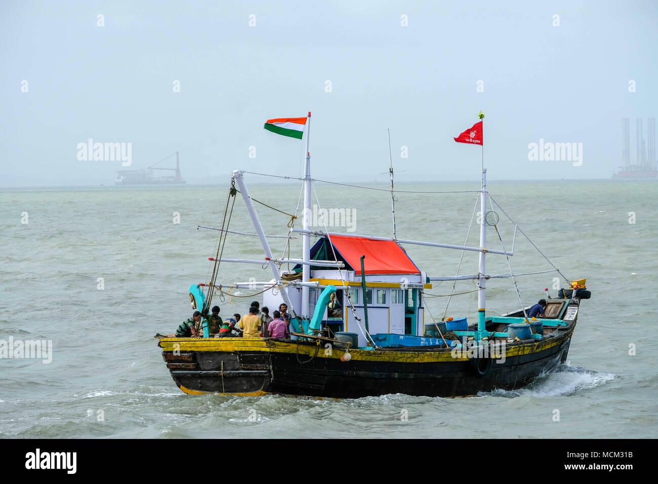 Wooden fishing vessel flying Indian flag, sailing on the Arabian sea in Mumbai, India - Stock Image