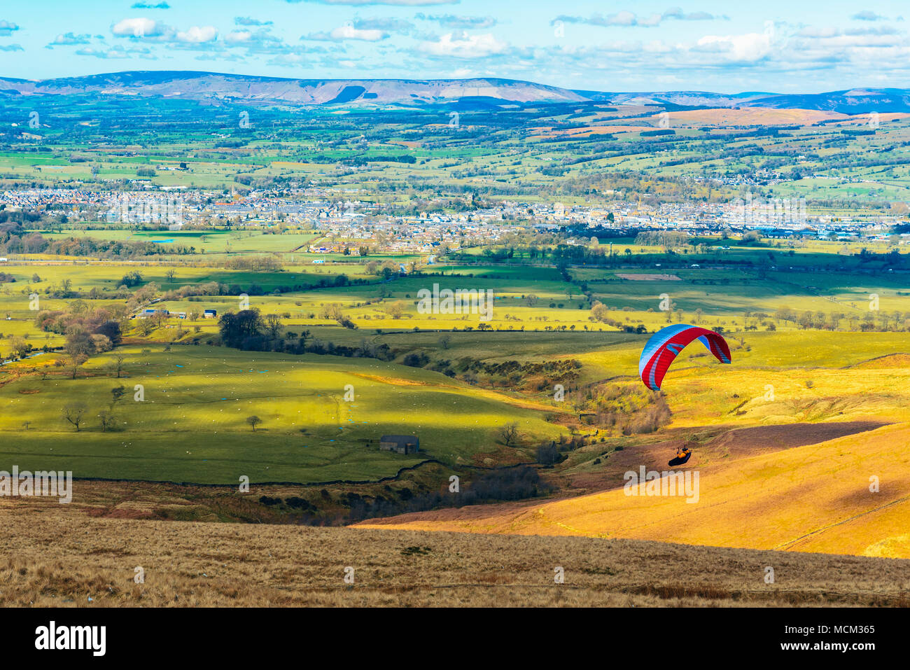 Paraglider above the Ribble Valley, Lancashire, England seen from the launching site on Pendle Hill with Clitheroe below and the Bowland Fells beyond Stock Photo