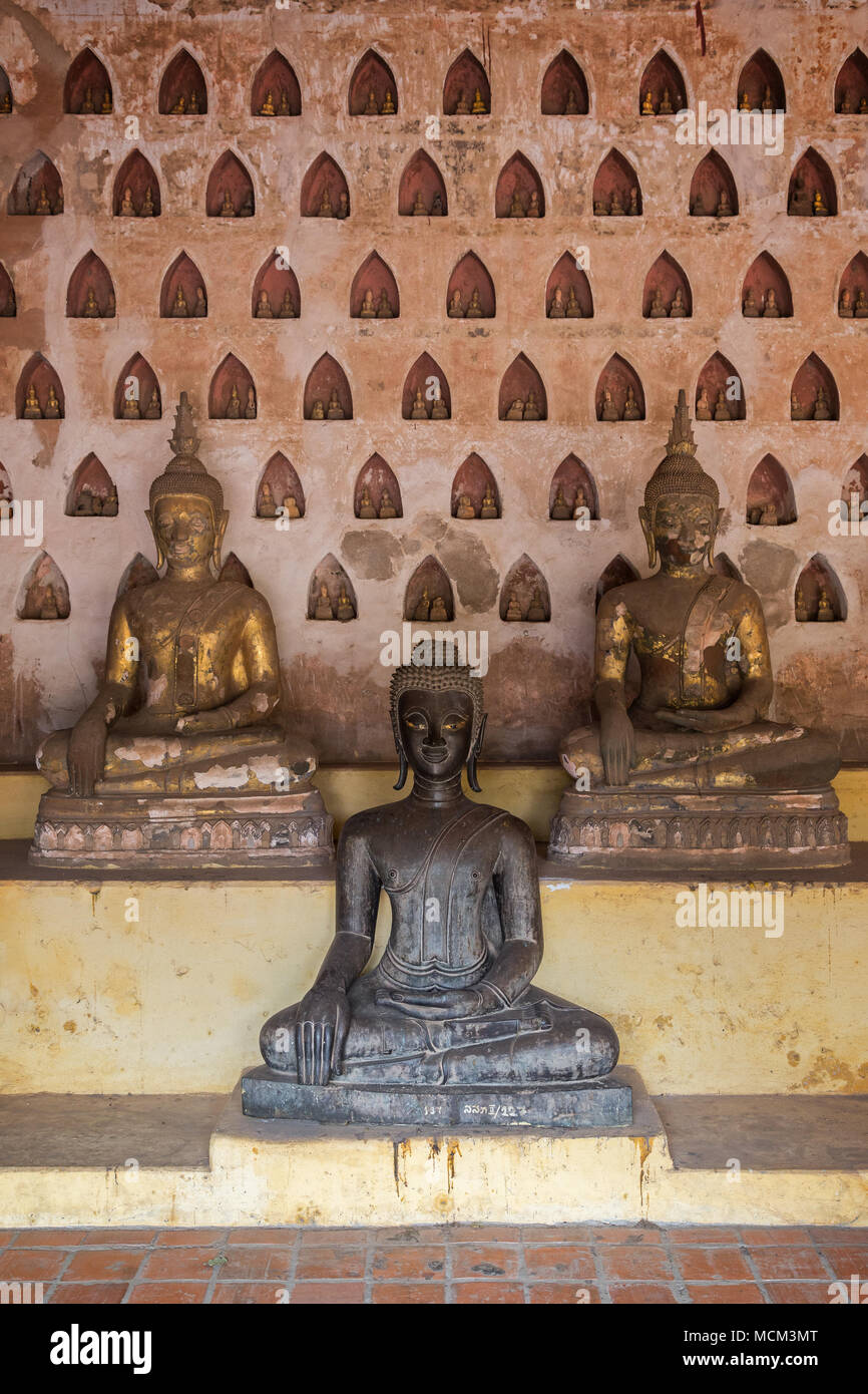 Front view of three old and aged Buddha statues at the Wat Si Saket (Sisaket) temple's cloister in Vientiane, Laos. - Stock Image