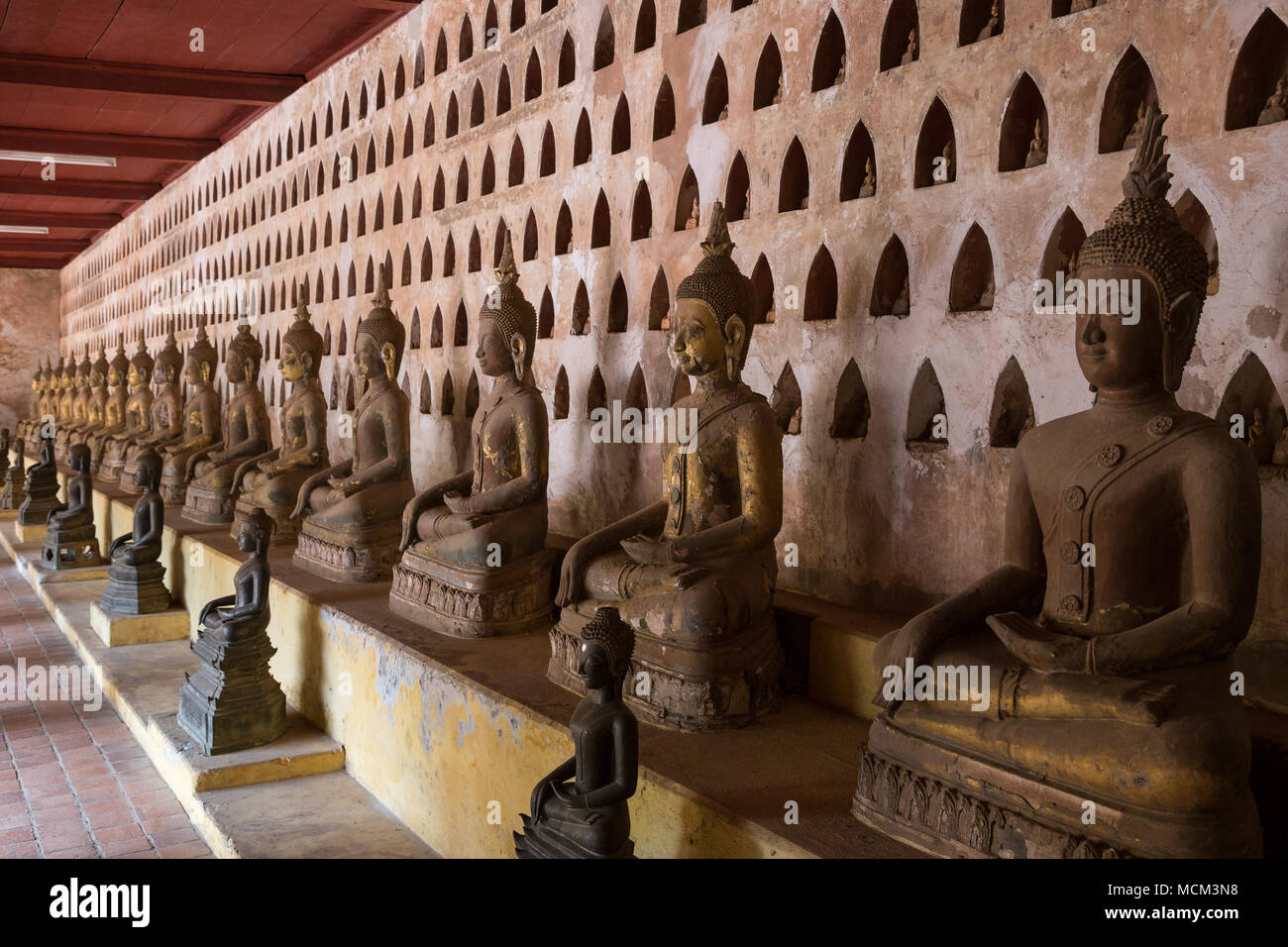 View of many old and aged Buddha statues at the Wat Si Saket (Sisaket) temple's cloister in Vientiane, Laos. - Stock Image