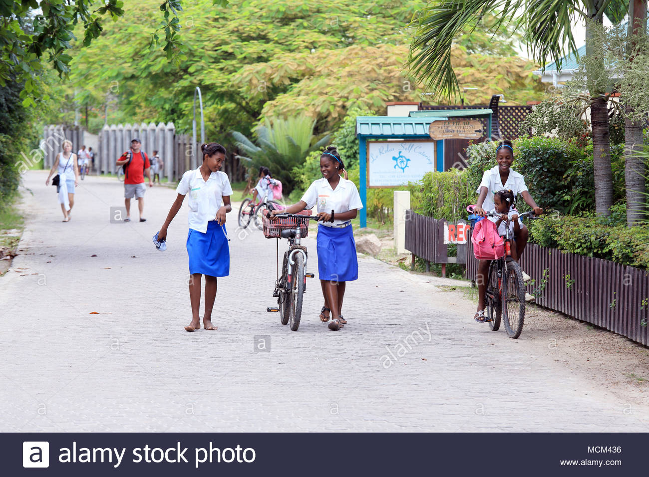 La Passe, La Digue Island, Seychelles - March 5, 2014: Students leaving the school on bicycles. - Stock Image