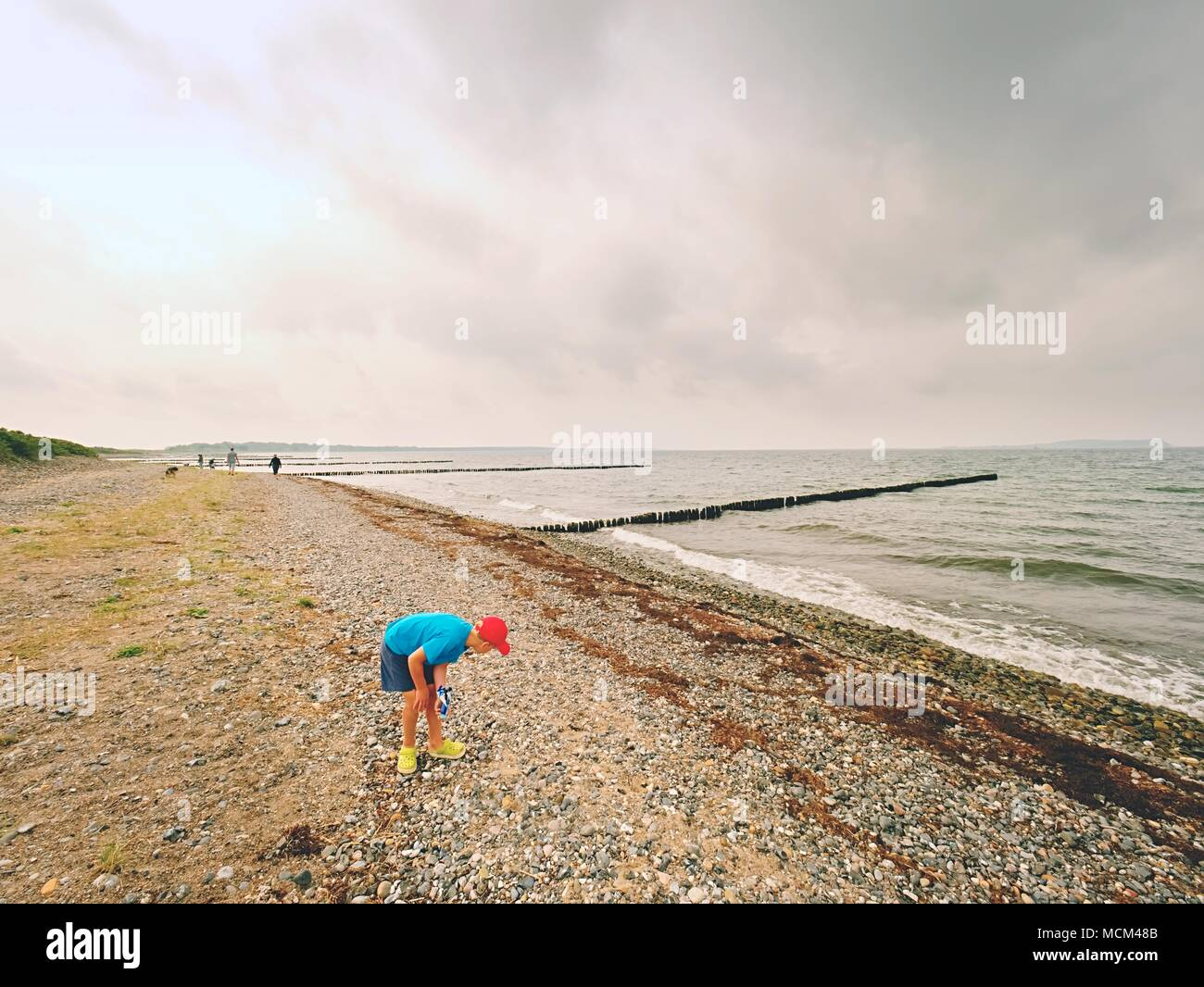 A thoughtful blond boy staying on beach near water.  Long stony beach with wooden breakwater to protect a coast  from the force of sea waves. Stock Photo