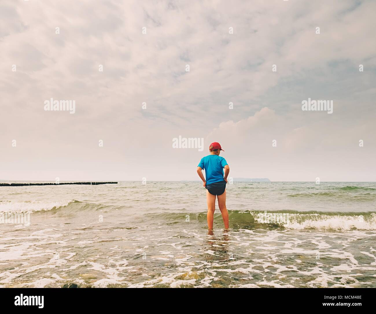 Children on the beach go into the ocean. Kid play in the waves of foamy sea. - Stock Image