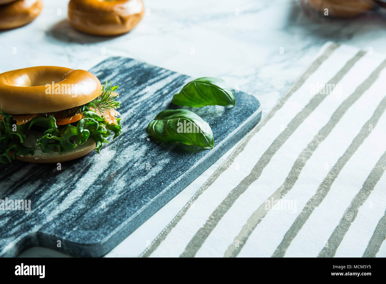 Salmon bagel on a stone cutting tablet with basil leaves on the side. - Stock Image