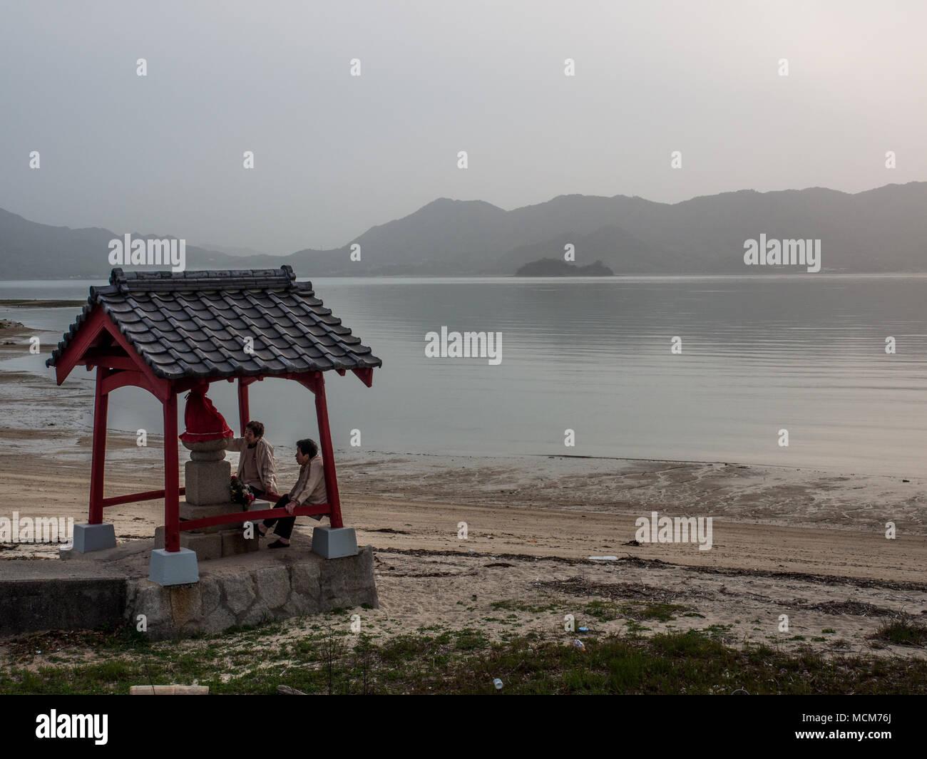 Two women at small sea side Buddhist shrine Innoshima, Seto Inland Sea, Japan Stock Photo