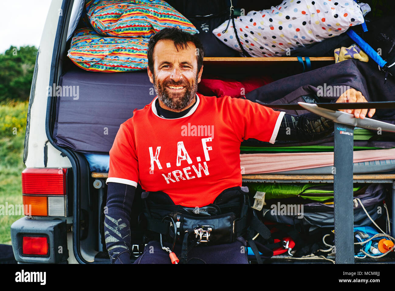 A lifestyle portrait of a kite surfer sitting outside his camper van - Stock Image