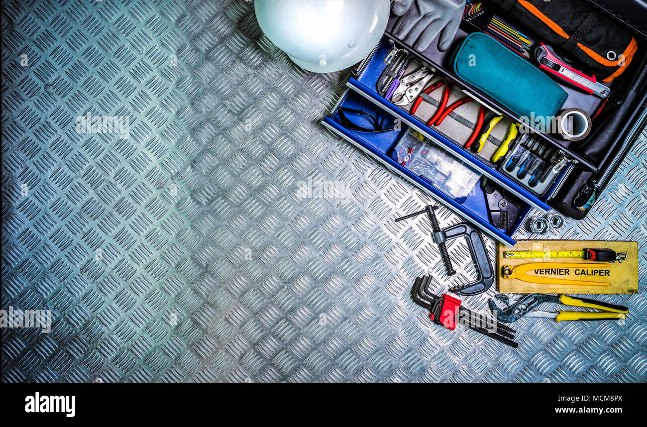 Top view of tools box and helmet on checkered plate background in workshop. Service tools set. Home building and electrical tools. Plumber hand tools. - Stock Image