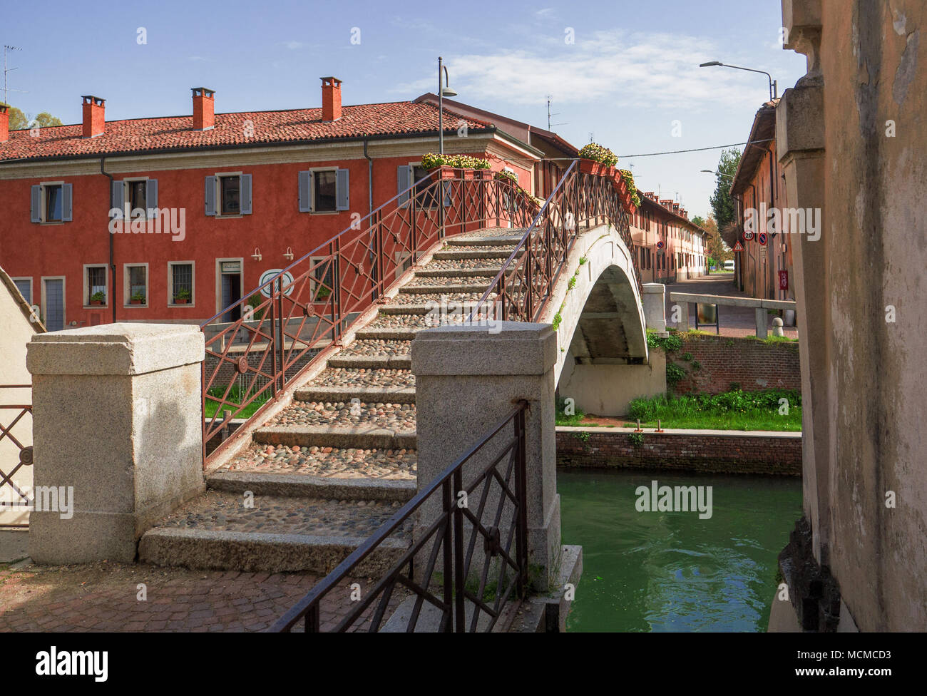 canal crossed by a cobblestone bridge, to move the houses of the village in the province of Milan, Italy - Stock Image