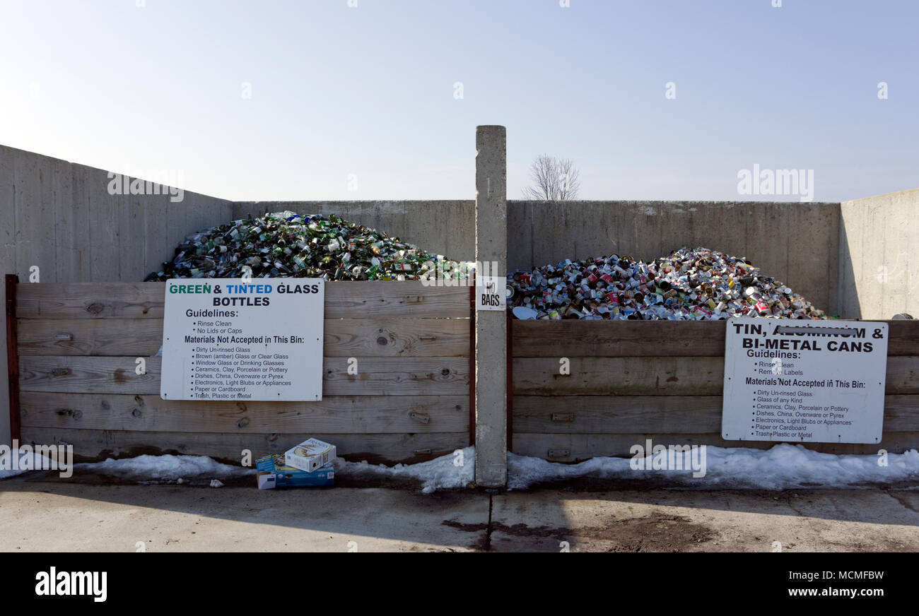 Metal cans and green and tinted glass bottles in community recycling collection bins with signs displaying guidelines - Stock Image