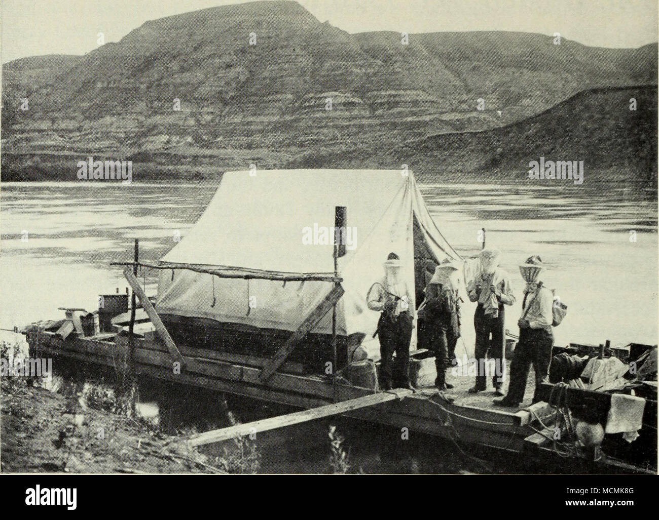 . Expedition from the American Museum of Natural History under Dr. Barnum Brown, in the Edmonton badlands of the Red Deer River, 1912. The fossil hunters wear nets for protection against mosquitoes. A.M.N.H., No. 18547. Soon the scow was floating between badland exposures of the Edmonton formation. Brown, used to the extensive badlands of South Dakota and Montana, thought of the vaHey as a canyon. Before the short season ended the scow was piled with specimens wrapped in the plaster and burlap casings, the first from Canada to be collected in this manner. In 1911 Brown continued his prospectin - Stock Image
