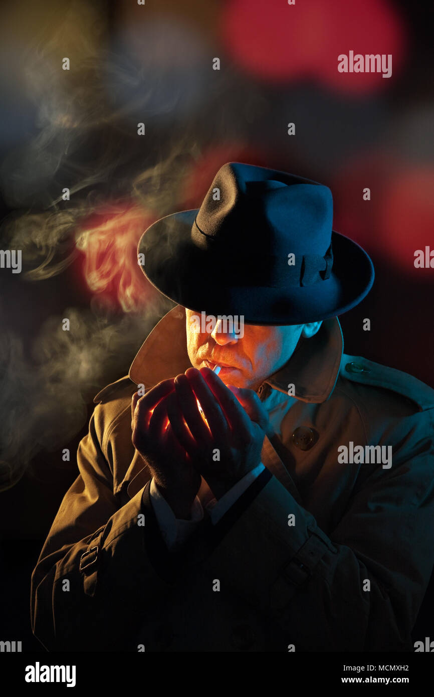 Private detective lighting a cigarette, film noir style - Stock Image