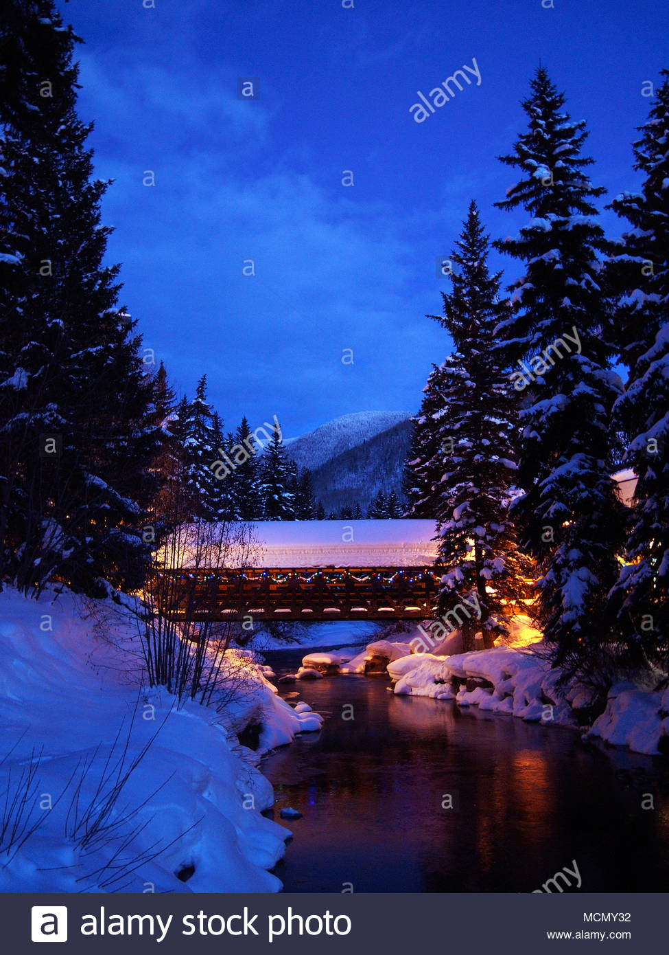 Vail, Colorado; view of the town at dusk, Gore Creek Covered Bridge - Stock Image