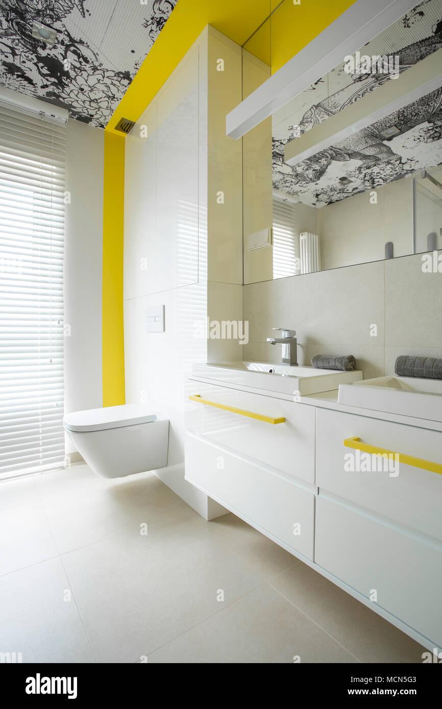 Trendy, modern, white bathroom interior design with creative yellow elements Stock Photo