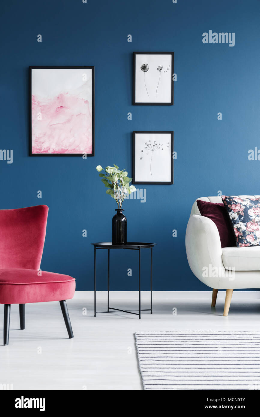 Flowers on black table between red chair and sofa in blue living room interior with posters