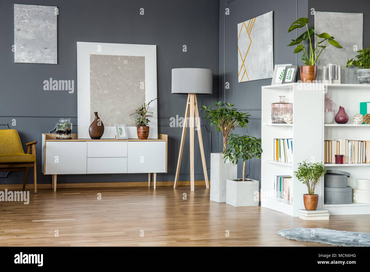 Books On White Bookshelf And Plants In Floral Grey Living Room
