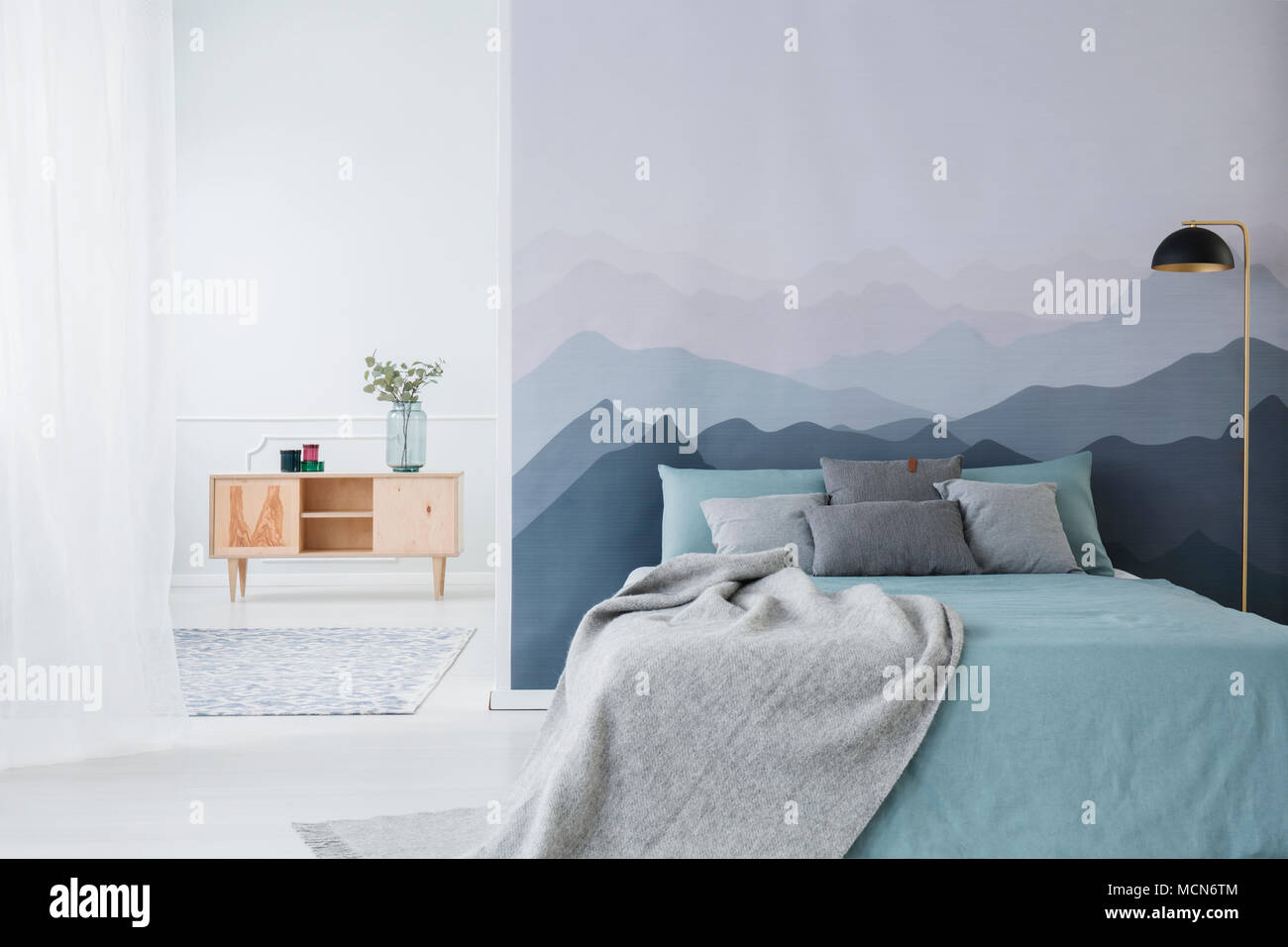Best Wallpaper Mountain Bedroom - blue-bed-with-grey-blanket-against-mountain-wallpaper-in-simple-bedroom-interior-with-wooden-cupboard-MCN6TM  Collection_73813.jpg