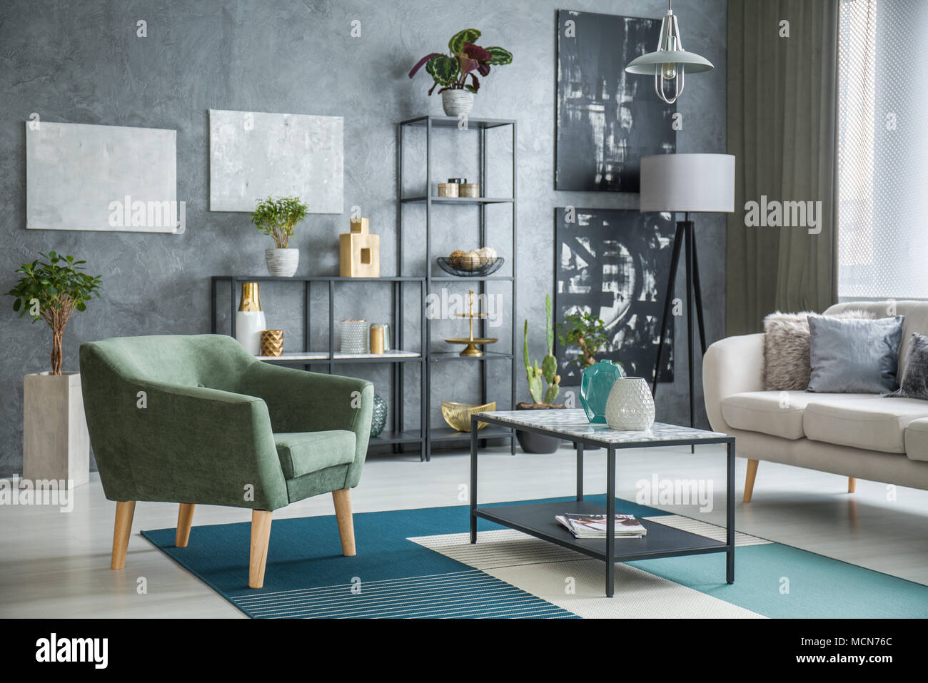 Green Armchair Standing Next To A Metal Table With Marble Pattern Placed In Industrial Living Room Interior With Plants And Decor Stock Photo Alamy
