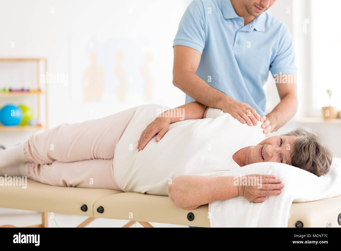 Physiotherapy performed by a physiotherapist on an happy old woman at the hospital - Stock Image