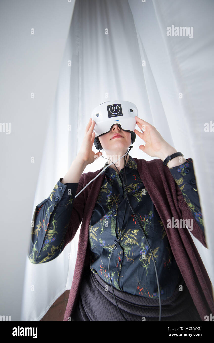 17 April 2018, Osnabrueck, Germany: An exhibition assistnat wearing the virtual reality glasses for the installation 'Rhizomat VR' by the artist Mona el Gammal. The 31st European Media Festival is running from 18 to 22 April, the related exhibition from 18 April until 21 May 2018. Photo: Friso Gentsch/dpa - Stock Image