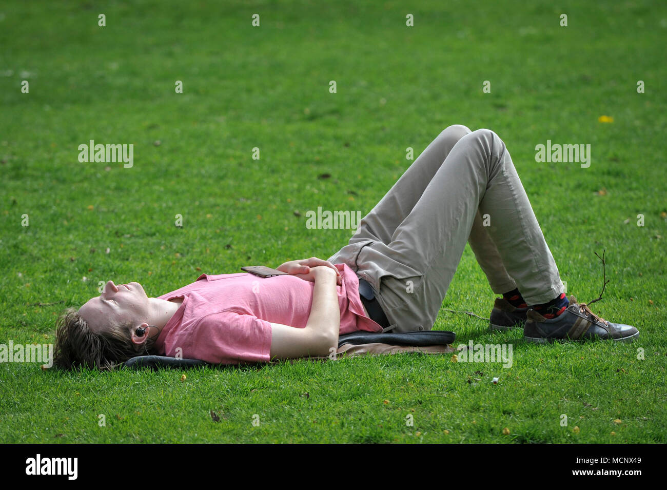 London, UK.  17 April 2018.  UK Weather: A man snoozes during warm weather in St. James's Park.   Much warmer temperatures of 25C are forecast to arrive in the UK in the next few days.  Credit: Stephen Chung / Alamy Live News - Stock Image