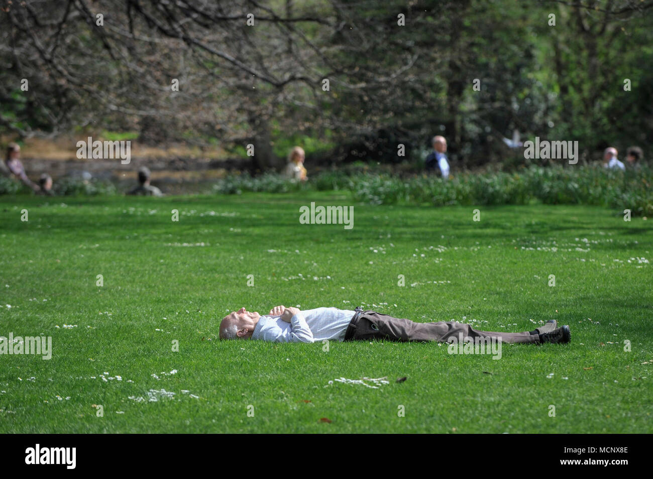 London, UK.  17 April 2018.  UK Weather: A man snoozes enjoying the warm weather in St. James's Park.   Much warmer temperatures of 25C are forecast to arrive in the UK in the next few days.  Credit: Stephen Chung / Alamy Live News - Stock Image