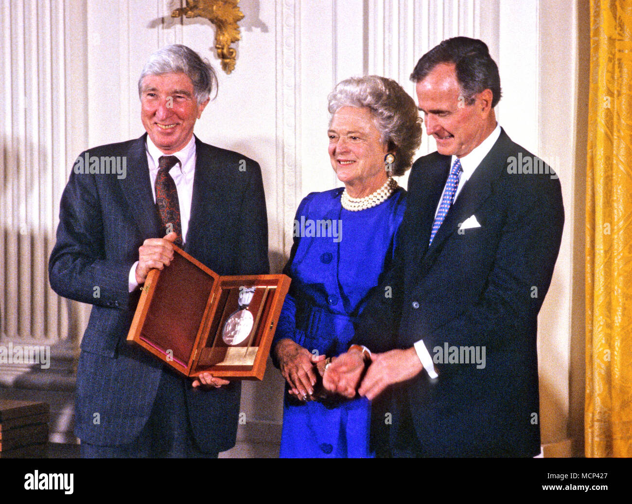 ***FILE PHOO*** BARBARA BUSH HAS PASSED AWAY (1925-2018) United States President George H.W. Bush and first lady Barbara Bush present the National Medal of Arts to American novelist, poet, short story writer, art critic, and literary critic John Updike during a ceremony in the East Room of the White House in Washington, DC on November 19, 1989. Credit: Ron Sachs/CNP /MediaPunch - Stock Image