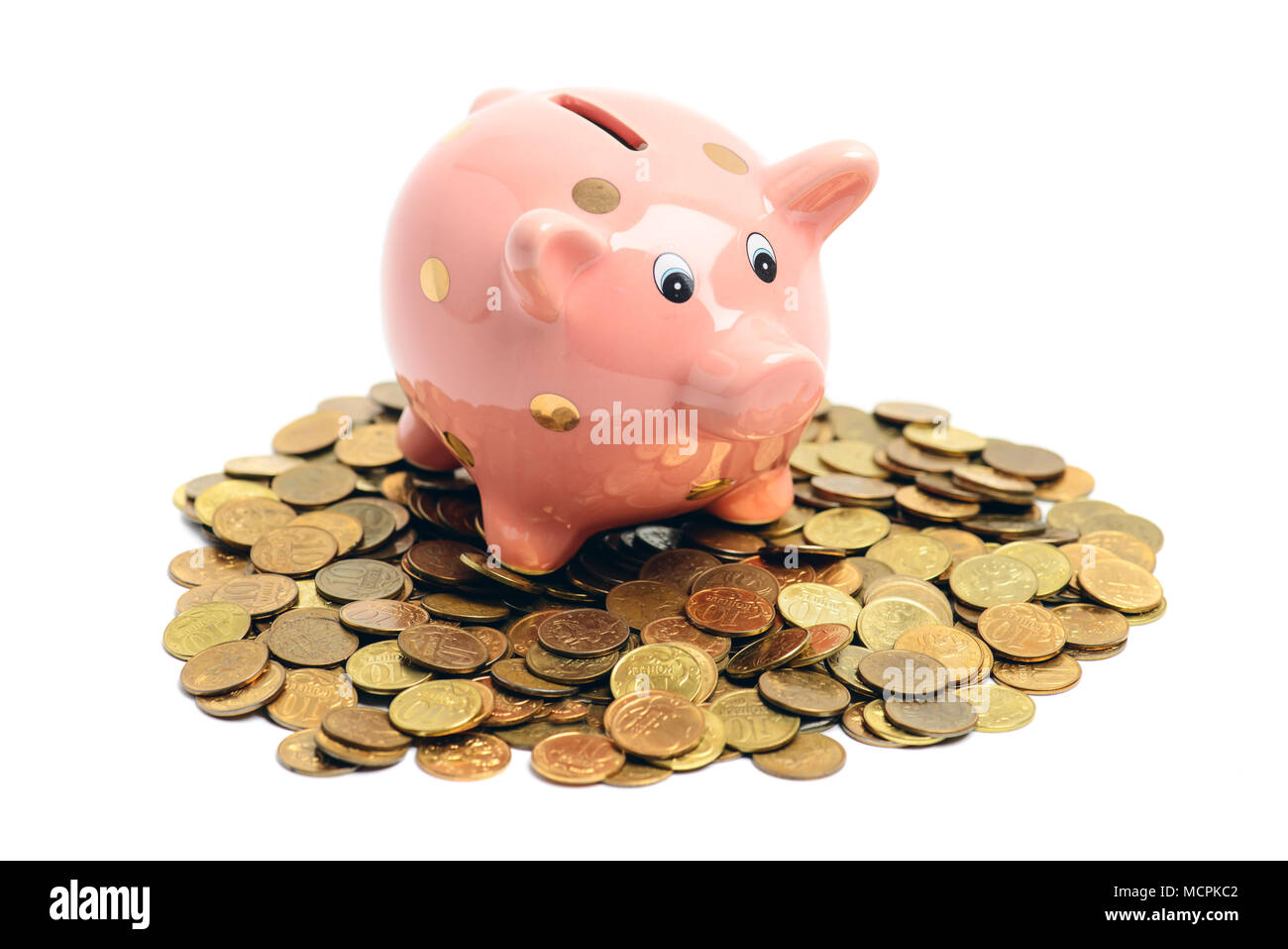 Lucky piggy coin bank on coin heap isolated on white background - Stock Image