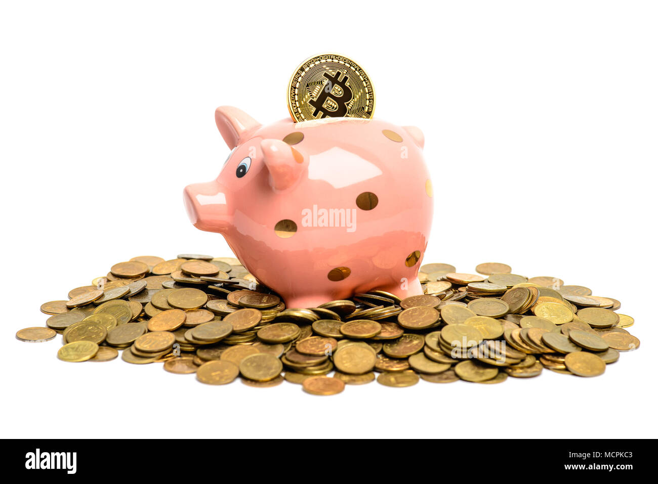 Pig coin bank on heap of money with bitcoin over white - Stock Image