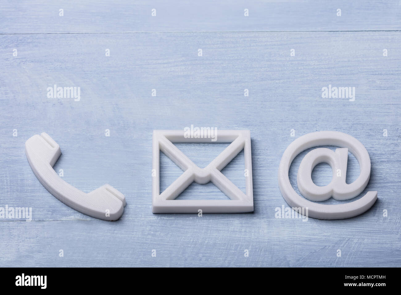 High Angle View Of White Phone, Email and Post Icons Isolated On Wooden Plank Stock Photo