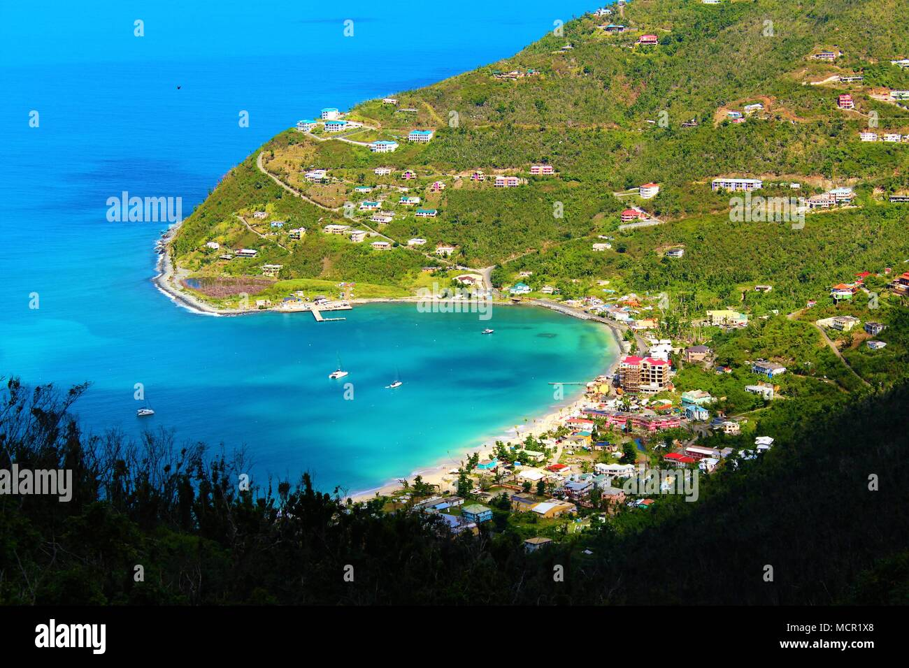 A view from high up on the island of Tortola, British Virgin Islands, onto a bay and coastal village below. February 28th 2018 - Stock Image