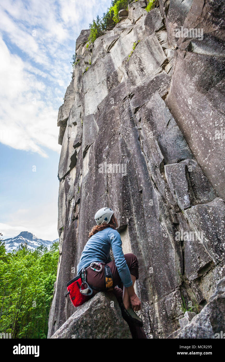 A woman putting on her climbing shoes and looking up at the rock face she's about to climb. Index climbing area, Washington Cascades, USA. - Stock Image