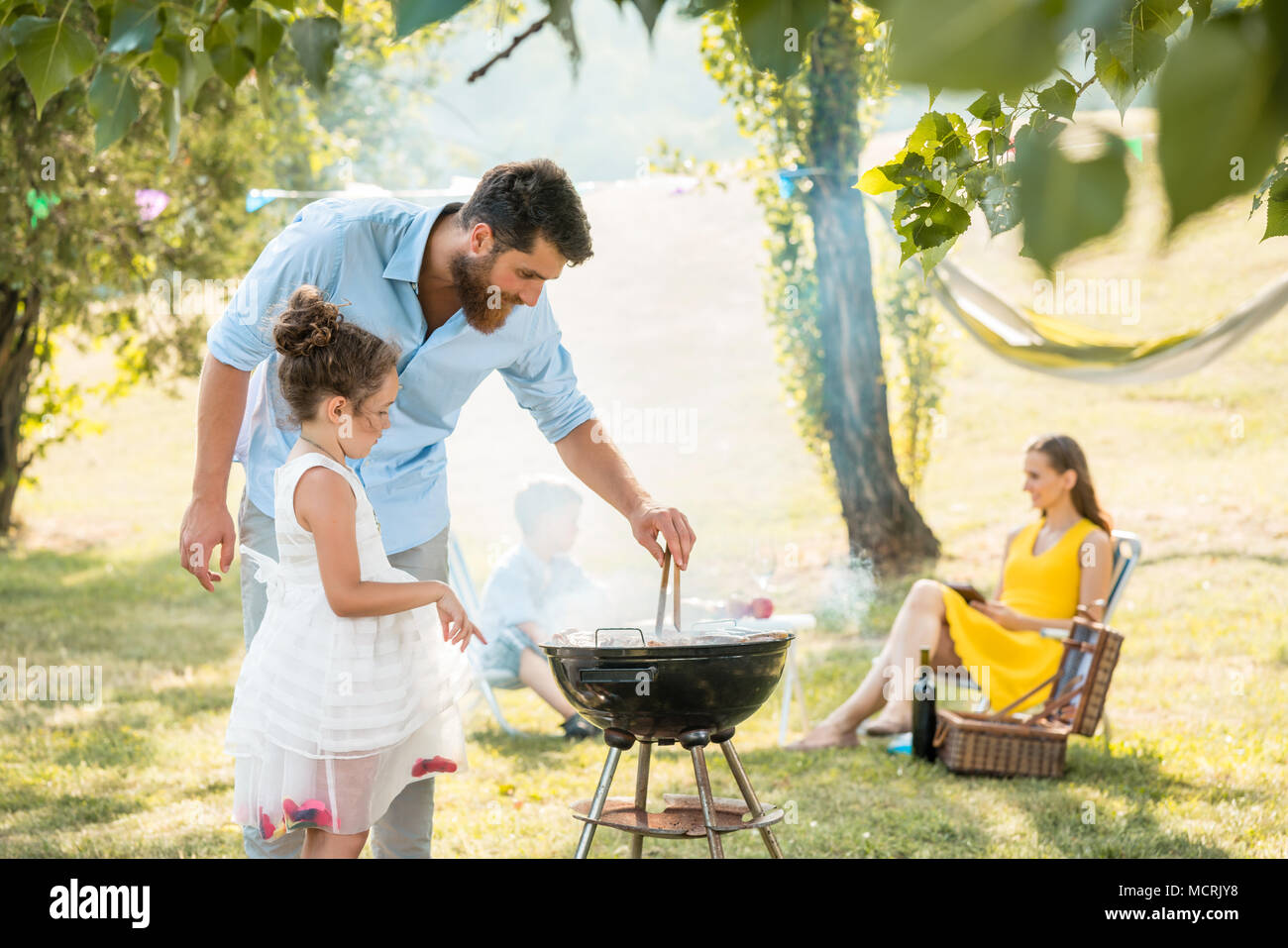 Girl watching father preparing meat on barbecue grill during family picnic - Stock Image