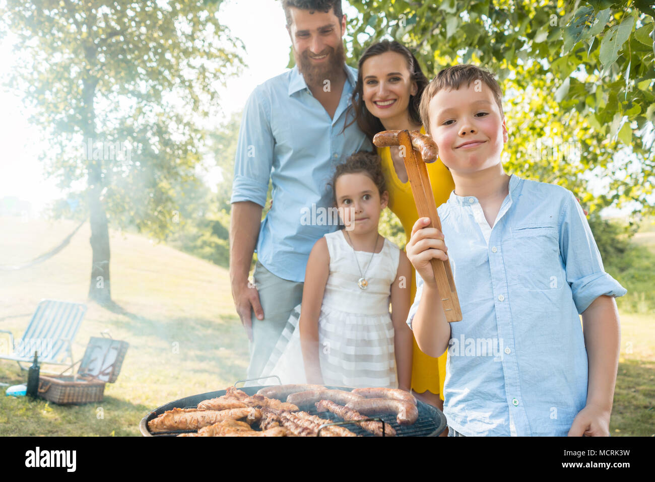 Portrait of happy family with two children standing outdoors near barbecue - Stock Image